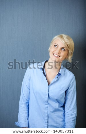Portrait of a smiling young blond woman standing against blue background looking up