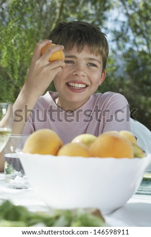 Portrait of a smiling young boy eating peach at garden table - stock photo