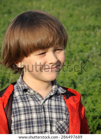 Portrait of a smiling young boy on the nature. Happiness, fashionable concept. Lifestyle.