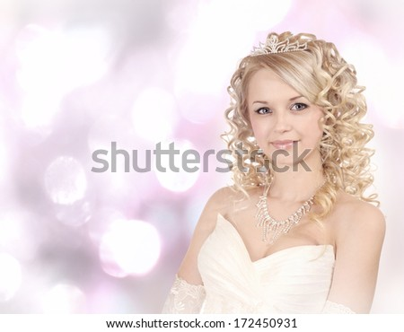 Portrait of a smiling young bride on light bokeh  background.
