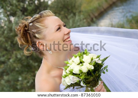 portrait of a smiling young bride on the nature - stock photo