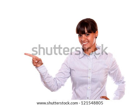 Portrait of a smiling young business woman pointing to her right while is looking at you standing over white background - copyspace - stock photo