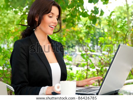 Portrait of a smiling young business woman using laptop at outdoor cafe, browsing internet. She is very interacted.