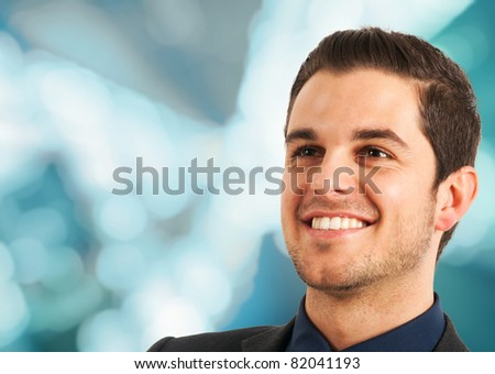 Portrait of a smiling young businessman. Blue blurred background. - stock photo