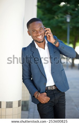 Portrait of a smiling young businessman calling by cell phone - stock photo