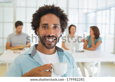 Portrait of a smiling young businessman having coffee with colleagues in background at office - stock photo