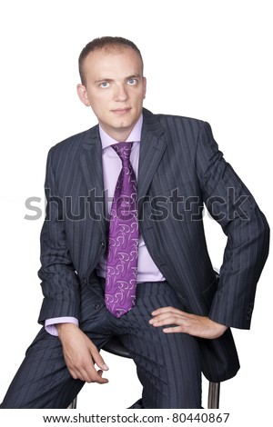 Portrait of a smiling young businessman sitting against isolated white background - stock photo