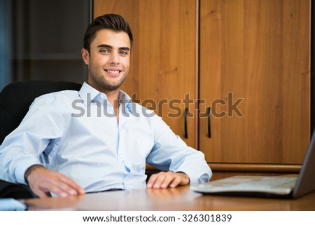 Portrait of a smiling young businessman sitting in his office - stock photo
