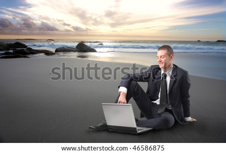 Portrait of a smiling young businessman sitting on a beach at sunset and using a laptop