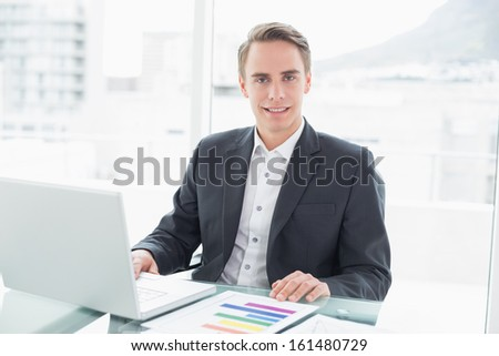 Portrait of a smiling young businessman with laptop sitting at office desk