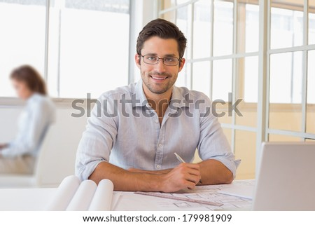 Portrait of a smiling young businessman working on blueprints at the office
