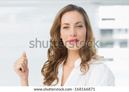 Portrait of a smiling young businesswoman against blinds in office