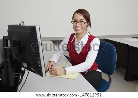 Portrait of a smiling young businesswoman sitting at office desk