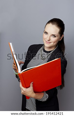 Portrait of a smiling young businesswoman, with long brunette hair, on gray studio background, holding an open red book or album in her hands - stock photo