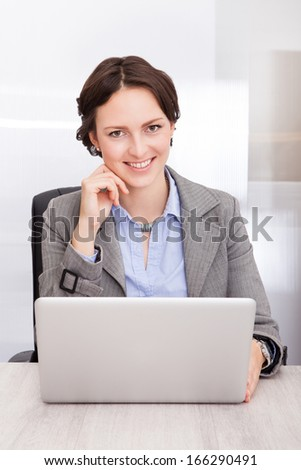 Portrait Of A Smiling Young Businesswoman Working On Laptop - stock photo