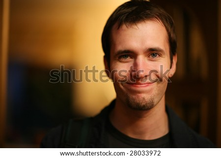 Portrait of a smiling young caucasian man. Shallow DOF. - stock photo