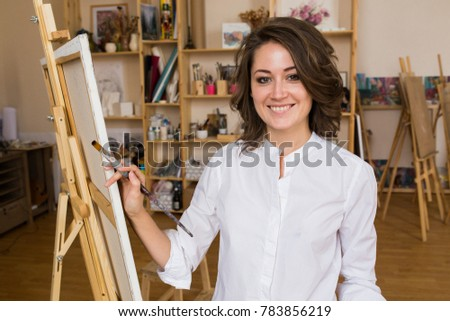 Portrait of a smiling young Caucasian woman writing in a white shirt, standing on canvas in studio