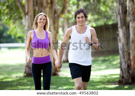 Portrait of a smiling young couple exercising in an outdoor setting while holding hands. The man is jogging, and the woman is walking. Horizontal shot. - stock photo