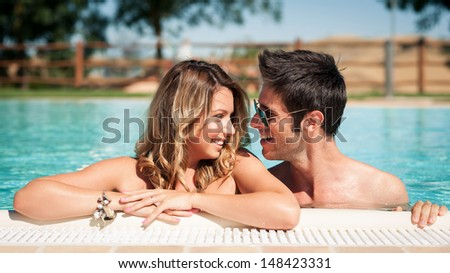 Portrait of a smiling young couple in a swimming pool. - stock photo
