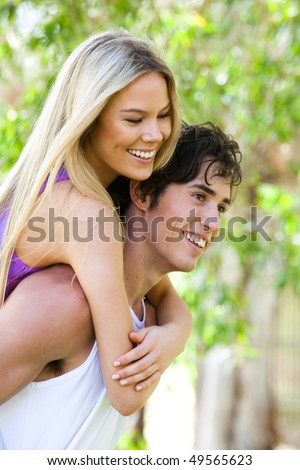 Portrait of a smiling young couple in an outdoor setting. The man is giving the woman a piggy-back ride. Vertical shot. - stock photo