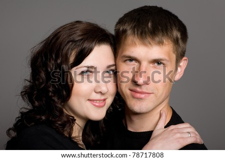 Portrait of a smiling young couple on a gray background. - stock photo