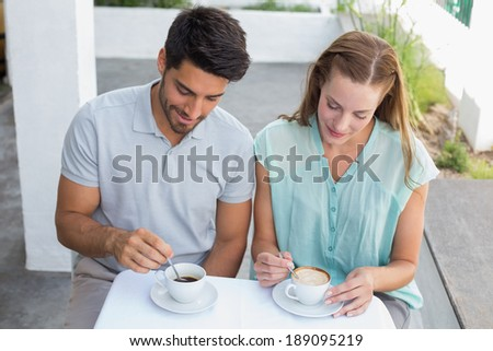 Portrait of a smiling young couple with coffee cups at the caf�©