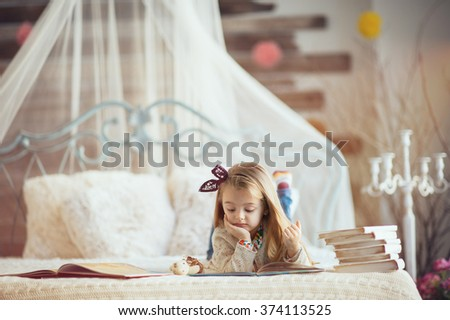 Portrait of a smiling young cute kid reading a book   the bed in a bright big white room  - stock photo