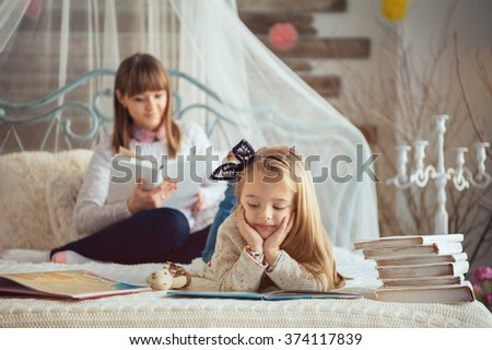 Portrait of a smiling young cute mother and daughter reading a book lying and relax in  the bed in a bright big white room  - stock photo