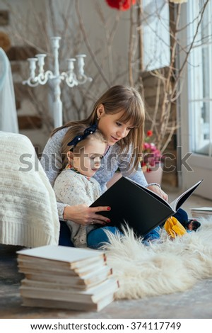 Portrait of a smiling young cute mother and daughter reading a book lying and relax on the floor in a bright big white room next to the window  - stock photo