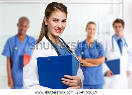 Portrait of a smiling young doctor in front of a group of medical workers - stock photo