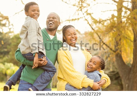 Portrait of a smiling young family laughing on an autumns day - stock photo