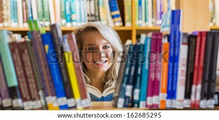 Portrait of a smiling young female student reading book amid bookshelves in the college library - stock photo