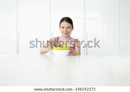 Portrait of a smiling young girl eating breakfast - stock photo