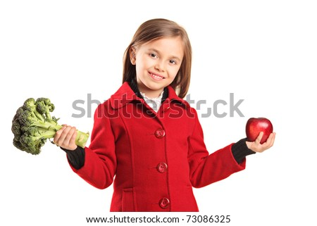 Portrait of a smiling young girl holding broccoli and apple isolated on white background