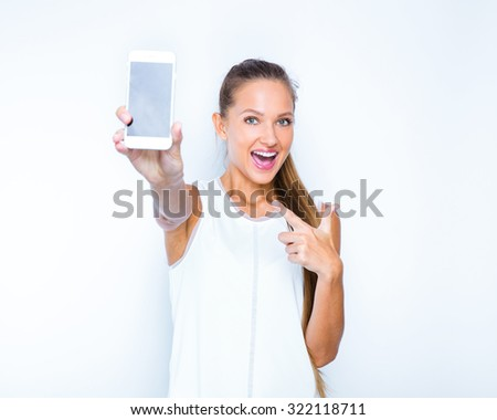 portrait of a smiling young girl holding in one hand smart phone and pointing on it with second hand. - stock photo