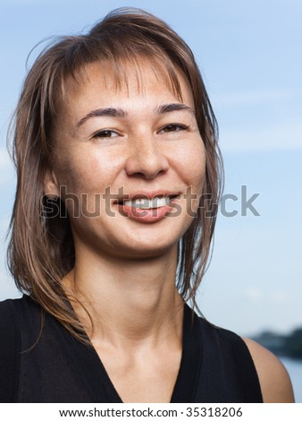 Portrait of a smiling young lady on light blue sky background