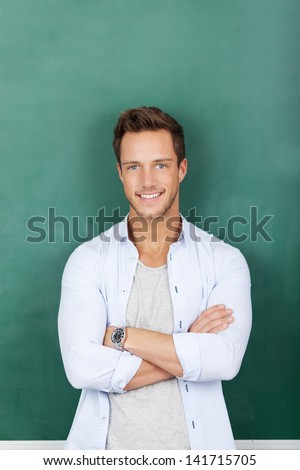 Portrait of a smiling young male teacher standing against green chalkboard - stock photo