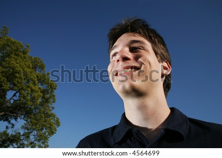 Portrait of a smiling young man, blue sky behind. - stock photo