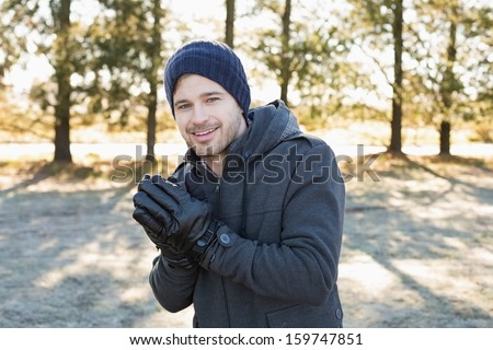 Portrait of a smiling young man in warm clothing shivering while having a walk in forest on a winter day - stock photo