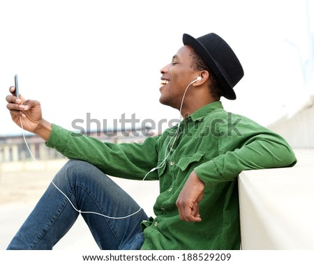 Portrait of a smiling young man listening to music on cellphone - stock photo