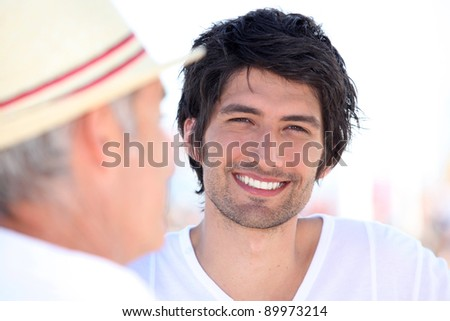 Portrait of a smiling young man outdoors - stock photo