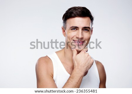 Portrait of a smiling young man over gray background - stock photo
