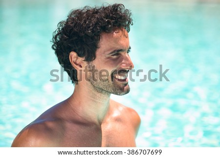 Portrait of a smiling young man relaxing in the water - stock photo