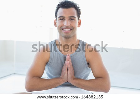 Portrait of a smiling young man sitting with joined hands against bright background - stock photo
