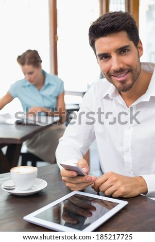 Portrait of a smiling young man text messaging in the coffee shop - stock photo