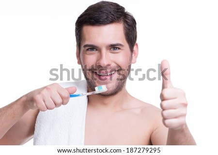 Portrait of a smiling young man with a toothbrush - isolated on white.