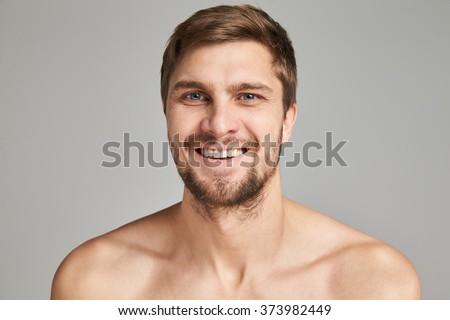 Portrait of a smiling young man with bare swimmers shoulders on a gray background, powerful, beard, charismatic, adult, brutal, athletic, edited photo, bright smile, white teeth smile, look in camera - stock photo