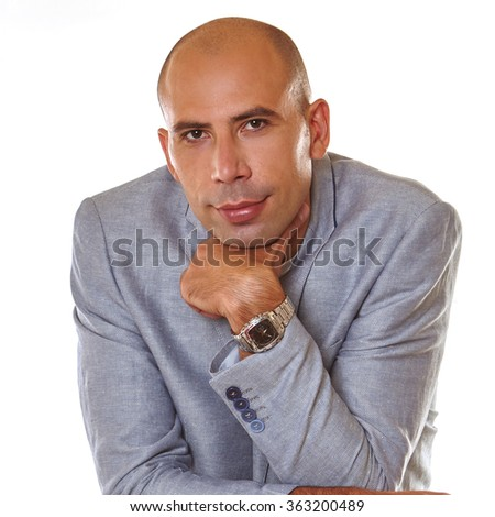 portrait of a smiling young man with he leans his chin on his left hand with watches, he dressed in at gray suit on the white background.  - stock photo