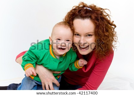 Portrait of a smiling young mother with her adorable newborn baby in a studio - stock photo