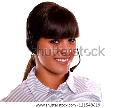 Portrait of a smiling young receptionist using earphone looking at you on isolated background - stock photo